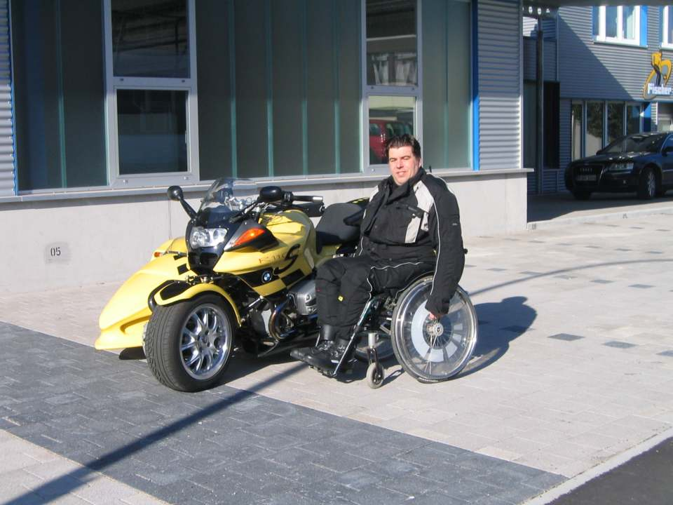 person an a Wheelchair in the front of a sidecar motocycle