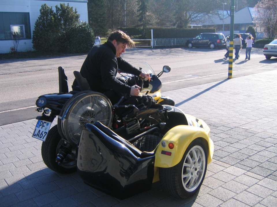 person in a Wheelchair control the parts of his chair on a sidecar motocycle