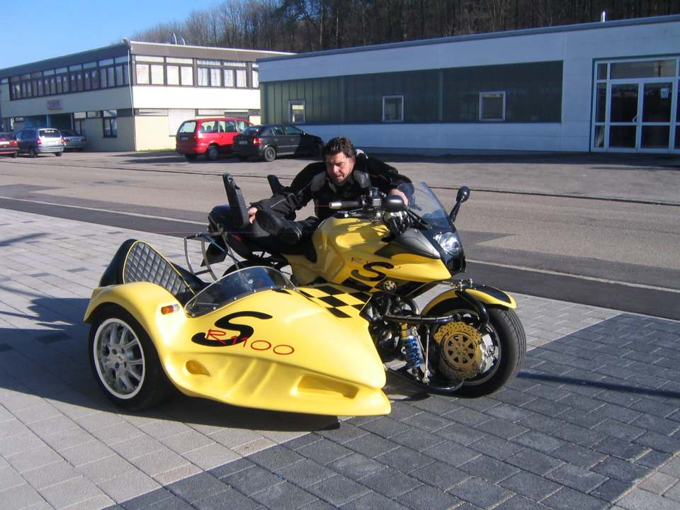 person an a Wheelchair in the climb on a sidecar motocycle